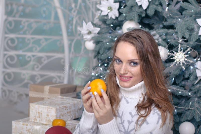 Flickan sitter nära askar med gåvor royaltyfri bild