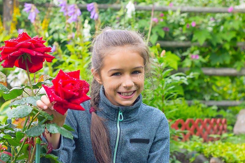 Flickan sitter nära den rosa busken i trädgården med ett bra lynne arkivfoton