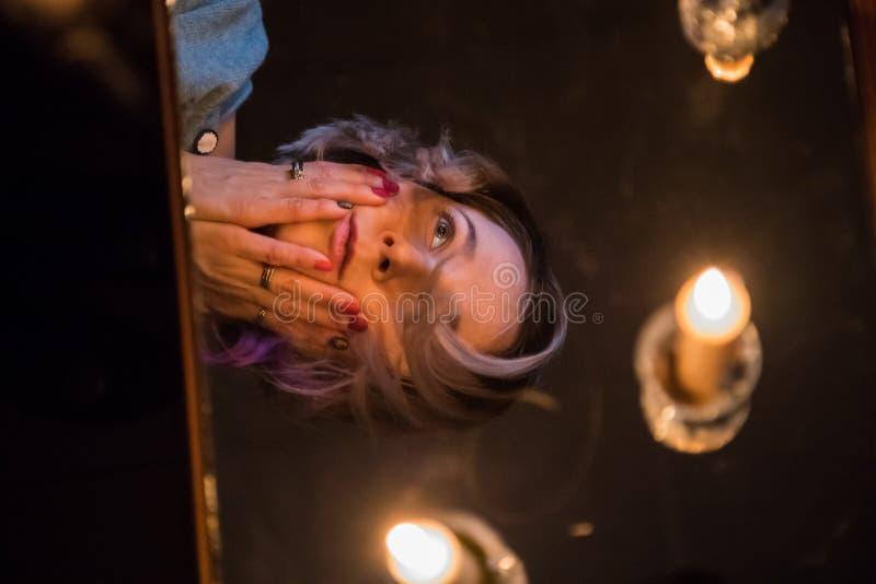Flickan sitter nära tabellen med stearinljus i ett mörkt rum och ser i spegeln royaltyfria bilder