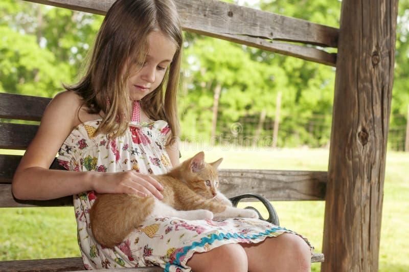 Flickan sitter och daltar en kattunge i hennes varv royaltyfria foton