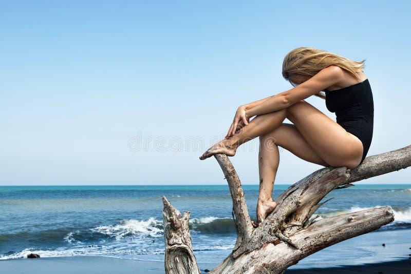 Flickan sitter på död trädfilial på den svarta stranden arkivbild