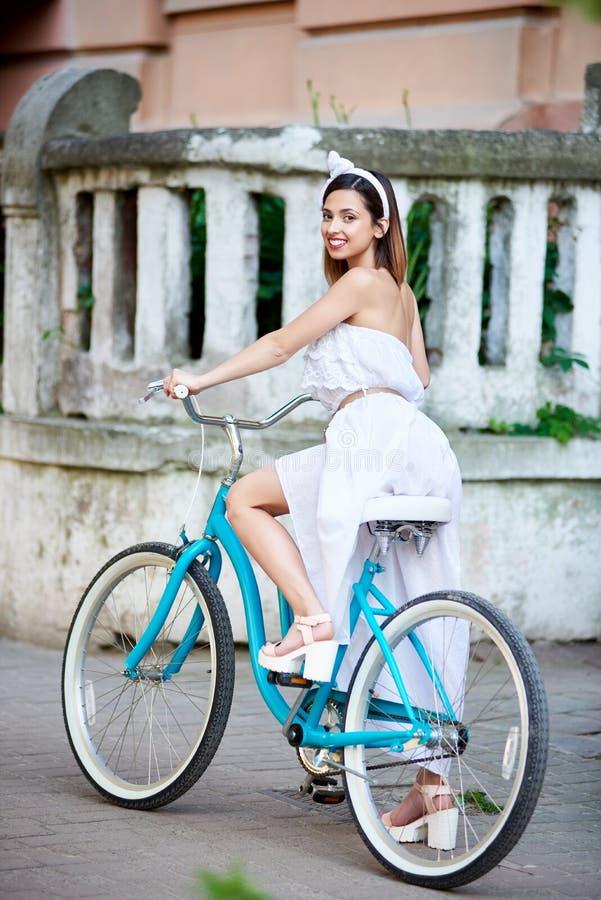 Flickan sitter på den retro cykeln mot den gamla byggnaden för bakgrunden fotografering för bildbyråer