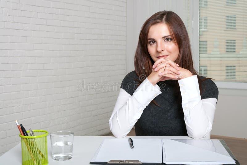 Flickan sitter på en arbetsplats royaltyfria foton