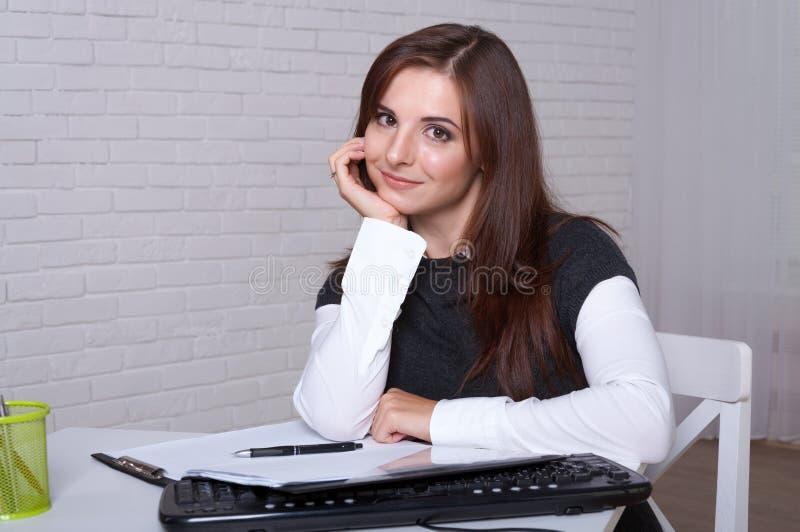 Flickan sitter på en arbetsstation propped hennes huvud på hennes hand royaltyfri foto