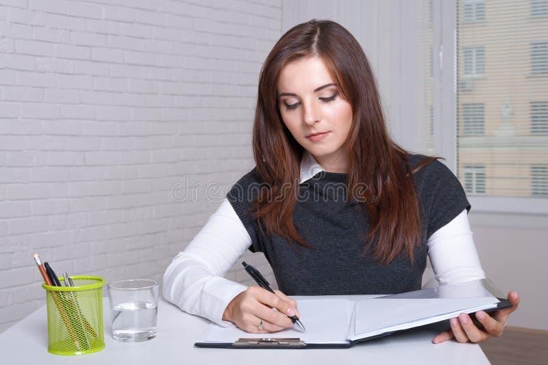 Flickan sitter på en arbetsstation skriver i dokumentmappen arkivfoton