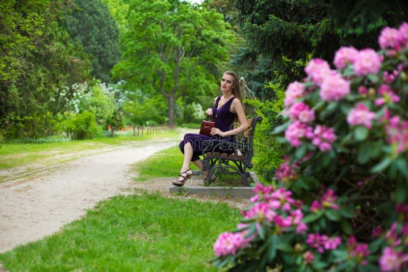 Flickan sitter på en bänk royaltyfri fotografi