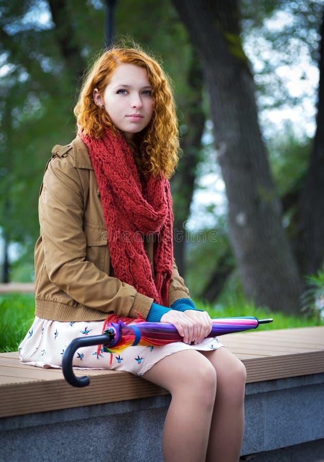Flickan sitter på en bänk. arkivfoton