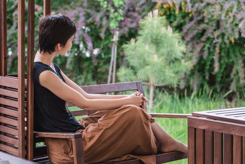 Flickan sitter på en bänk och ser hänsynsfullt in i avståndet relax arkivfoton