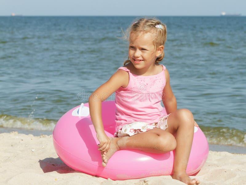 Flickan sitter på en cirkel för att simma nära havet arkivbilder