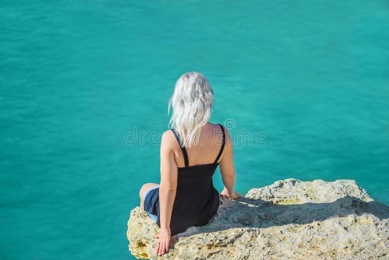 Flickan sitter på en klippa ovanför havet royaltyfria foton