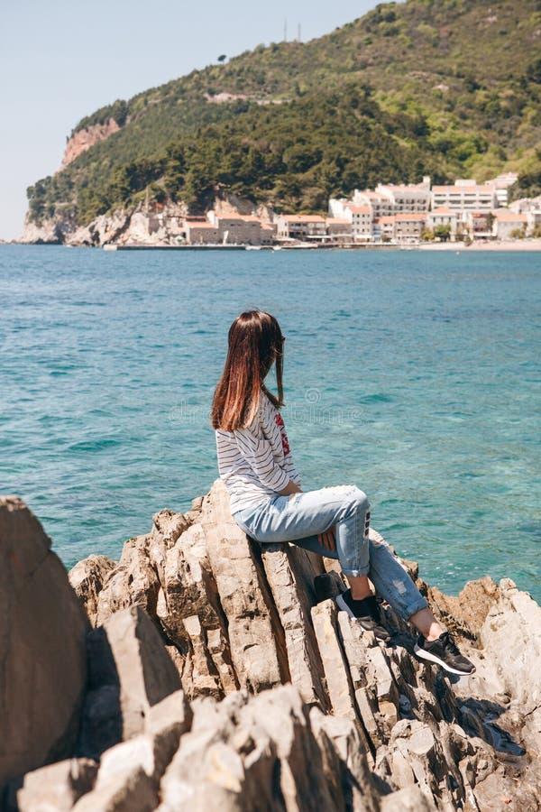 Flickan sitter på en stenig kust royaltyfri fotografi
