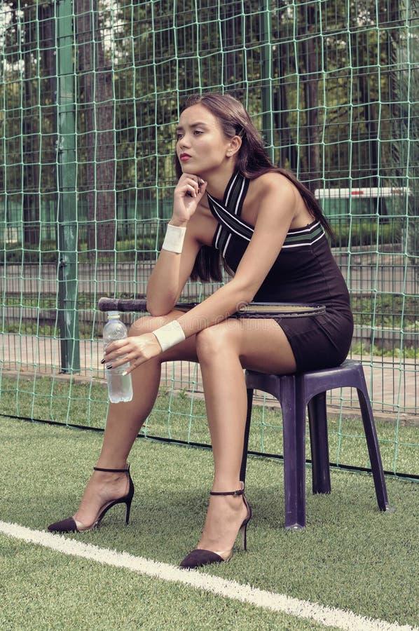 Flickan sitter på en stol med en vattenflaska royaltyfri foto