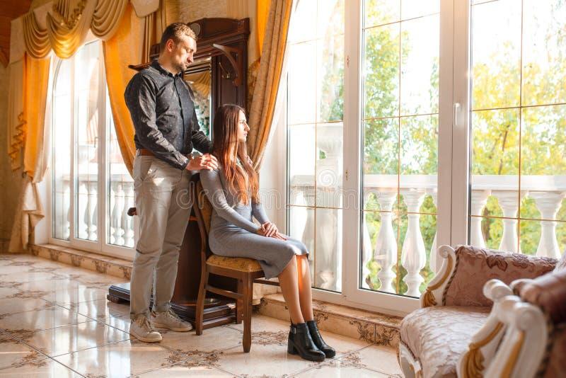 Flickan sitter på en stol, och grabben sätter bakifrån hans händer på hans skuldra royaltyfri fotografi