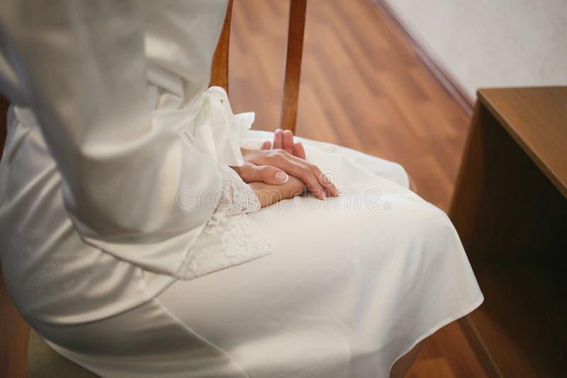 Flickan sitter på en stol som korsar hennes händer med perfekt manikyr Bröllopmorgon av bruden royaltyfri fotografi