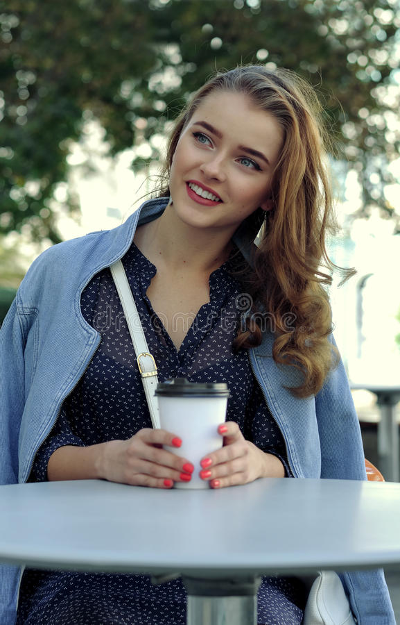 Flickan sitter på en tabell med en pappers- kopp för att dricka arkivbilder