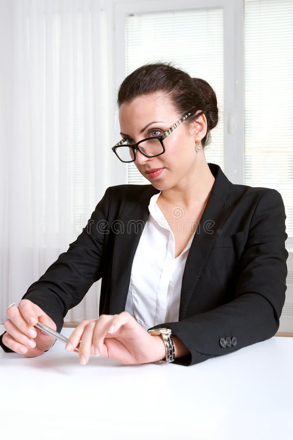 Flickan sitter på en tabell som ser över hans exponeringsglas royaltyfri foto