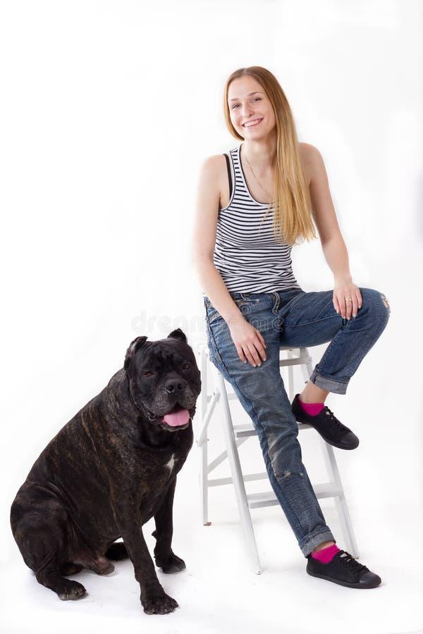 Flickan sitter på en trappstege hennes hund Cane Corso därefter arkivbilder