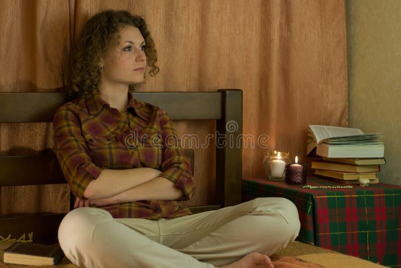 Flickan sitter på säng fotografering för bildbyråer