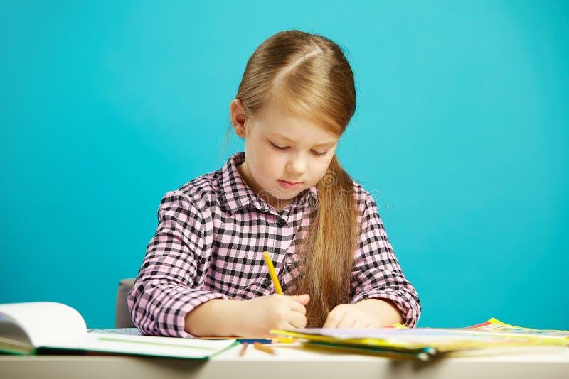 Flickan sitter på skrivbordet och skriver till anteckningsboken, på blått isolerad bakgrund Första väghyvel i skola royaltyfri bild