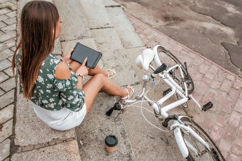 Flickan sitter på trappan i sommaren i staden I händer av minnestavlan är applikationen öppen i internet nära royaltyfria foton