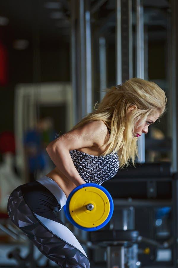 Flickan skakar hennes biceps arkivfoto