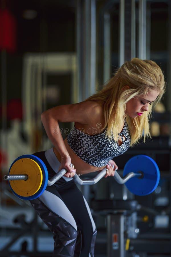 Flickan skakar hennes biceps royaltyfri foto