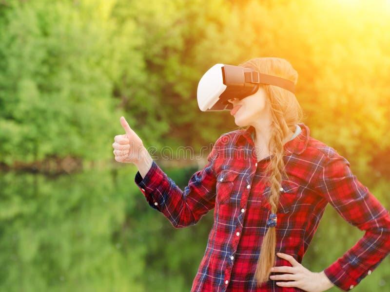 Flickan skjuter virtuell verklighetexponeringsglas, solnedgång i naturen, baksidasikt tum upp royaltyfri bild
