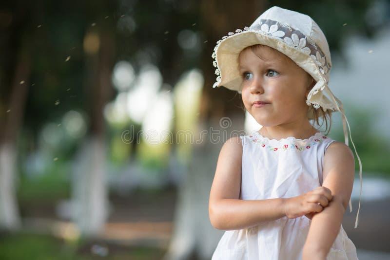Flickan skrapar hennes hand från en myggatugga arkivbild