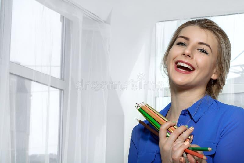 Flickan skrattar innehavblyertspennor i händer fotografering för bildbyråer