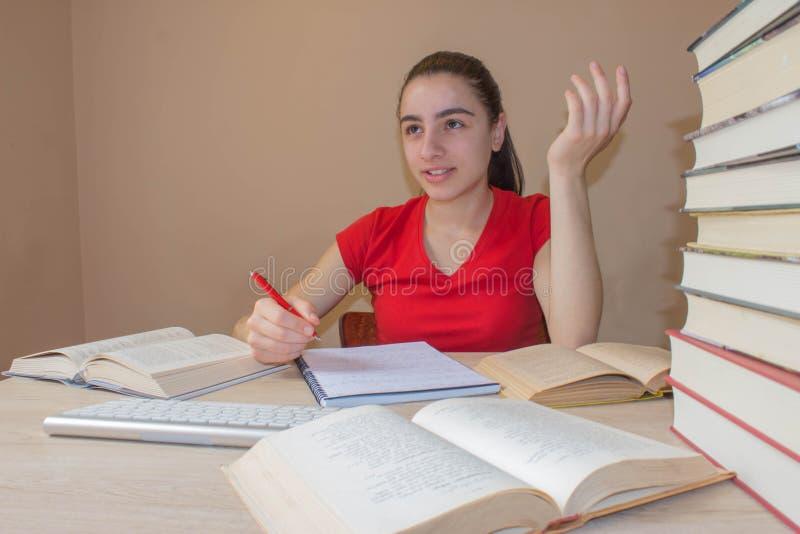 Flickan skriver i anteckningsbok mellan böcker ung attraktiv student Girl som studerar kurser royaltyfri fotografi