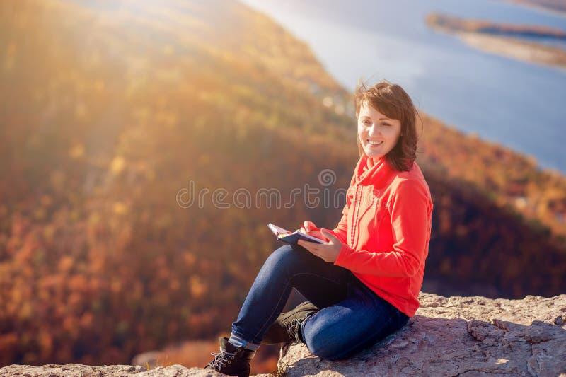 Flickan skriver i en anteckningsbok arkivbild