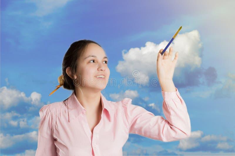 Flickan skriver i himlen med en borste royaltyfri bild