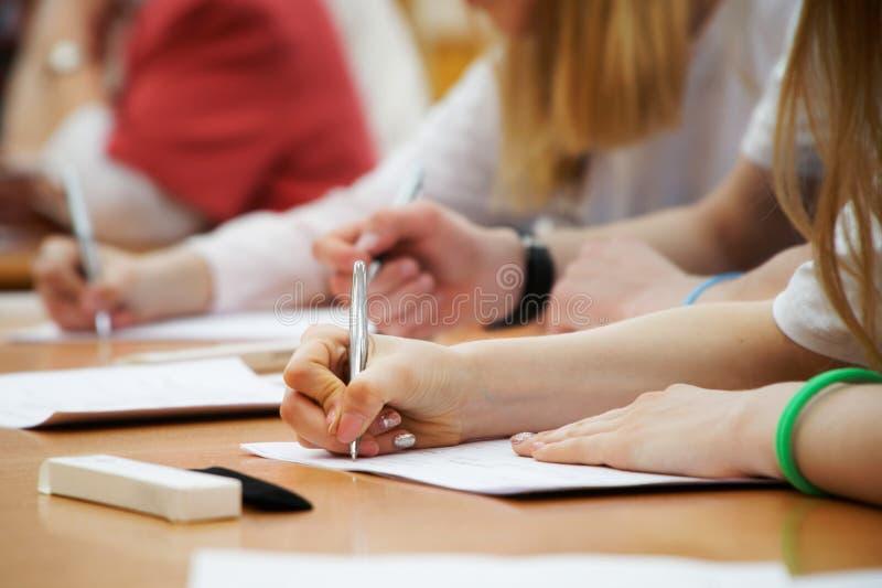 Flickan skriver med en reservoarpenna på ett stycke av papper under grupper på skola eller högskolan Undersökning examina arkivbild