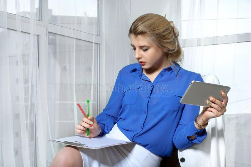 Flickan skriver sammanträde i en stol royaltyfri foto