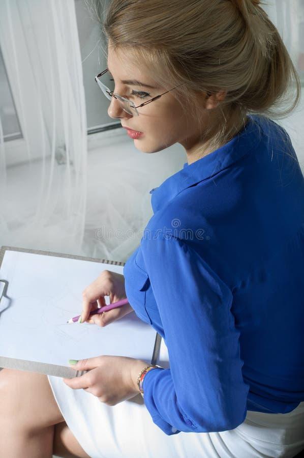 Flickan skriver sammanträde i en stol royaltyfri bild