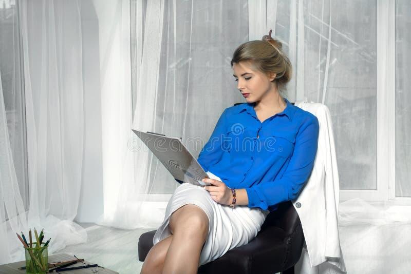 Flickan skriver sammanträde i en stol fotografering för bildbyråer