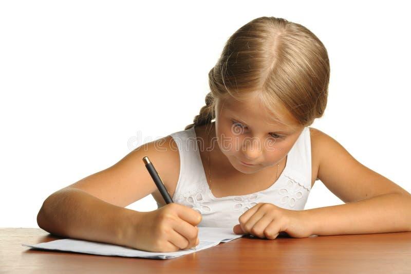 Flickan skriver till writing-böcker royaltyfria bilder