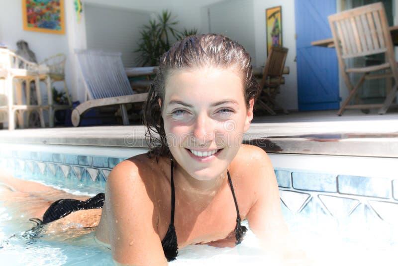 flickan solbadar i simbassängen i en svart baddräkt royaltyfri foto
