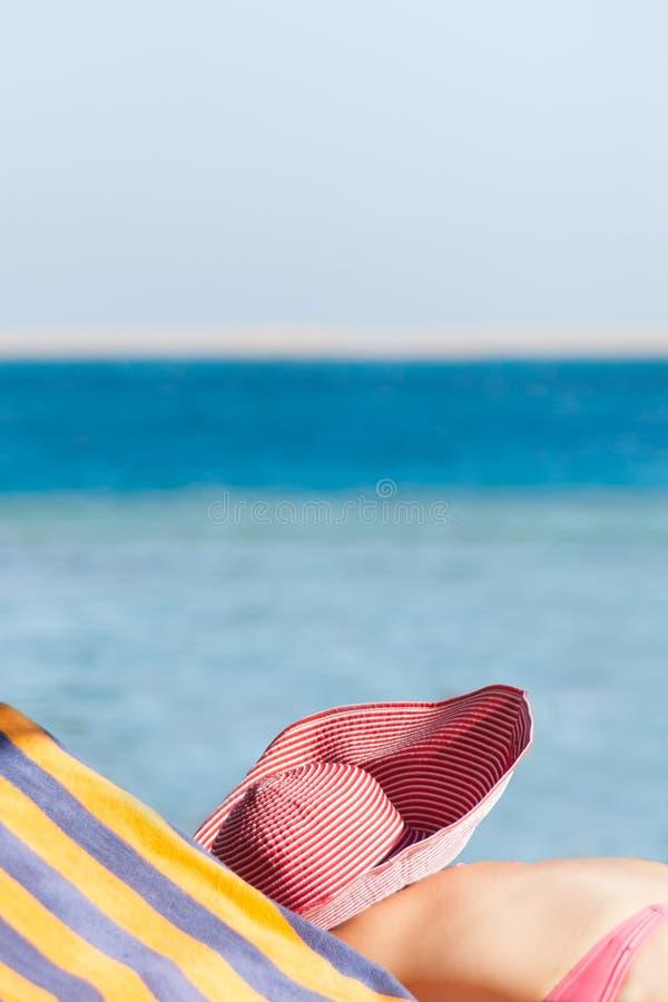 Flickan solbadar på kusten arkivfoto