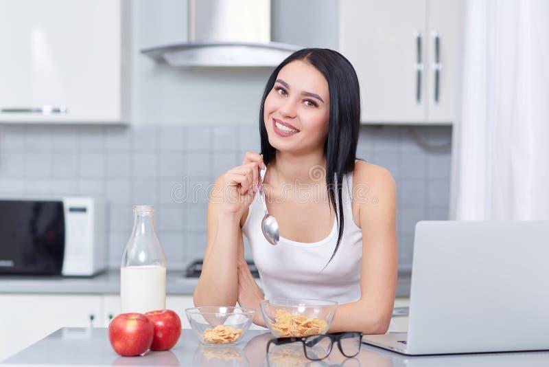 Flickan som äter ekflingor och, mjölkar arkivbilder