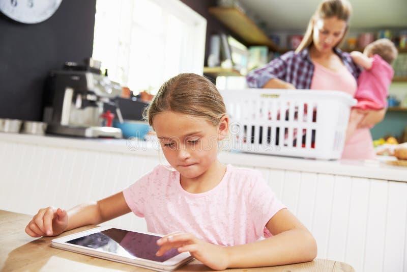 Flickan som använder den Digital minnestavlan som moder, sorterar tvätterit royaltyfria bilder