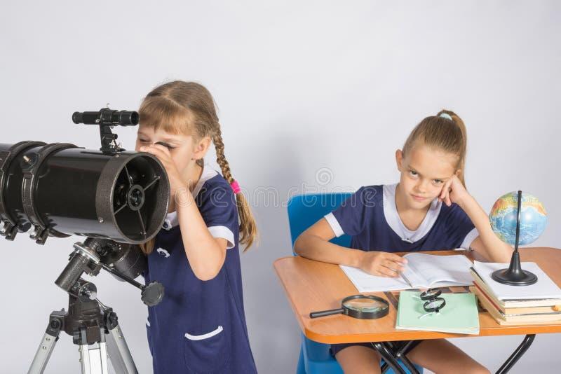 Flickan som astronomen ser himlen till och med ett teleskop, den annan flickan, sitter på tabellen royaltyfri foto