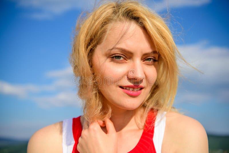 Flickan som behas med varmt solljus, ser avkopplad bakgrund för blå himmel Känselharmoni och fred lätt take Kvinnablondin royaltyfria bilder