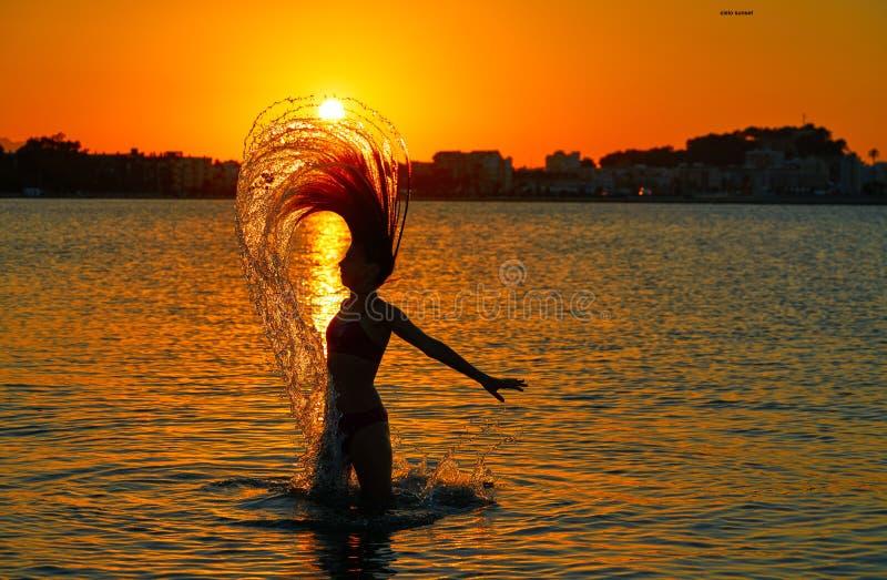 Flickan som bläddrar hår, bläddrar på solnedgångstranden arkivbild