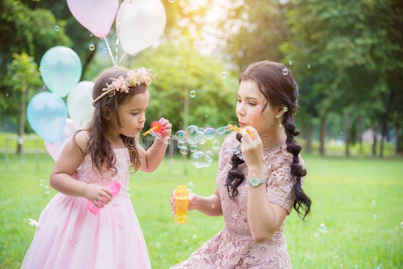 Flickan som blåser bubblor med hennes moder parkerar in royaltyfri foto
