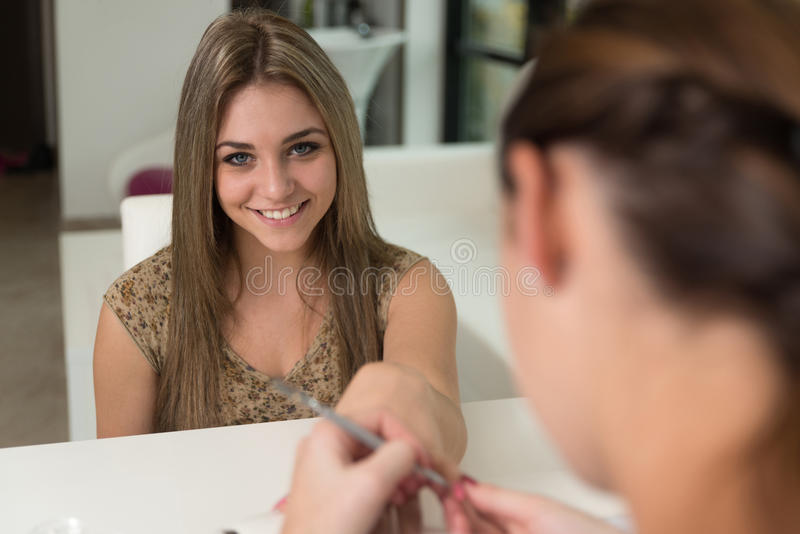 Flickan som får henne, spikar gjort i skönhetsalong royaltyfria foton