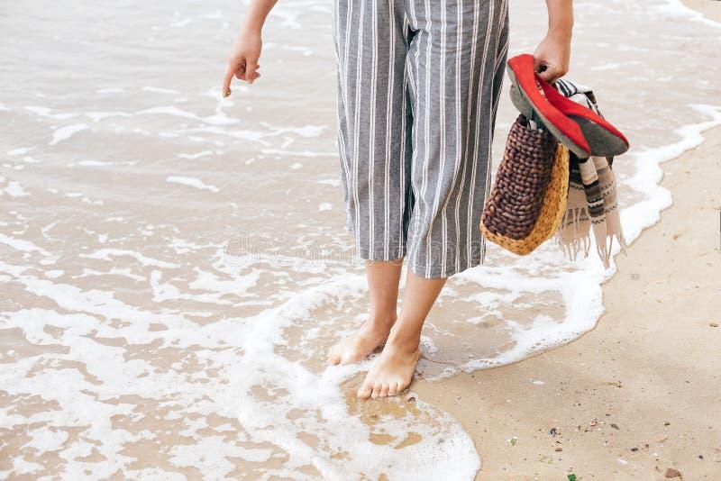 Flickan som f?rs?ker att skriva sommarord eller solsymbol p? den sandiga stranden p? havet, men v?gor f?rd?rvar tecknet Hello som royaltyfria foton