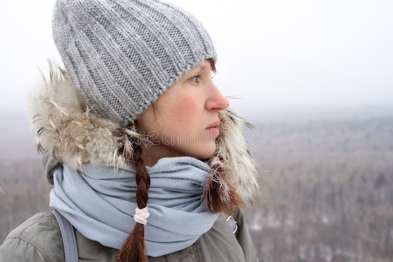 Flickan som fotvandrar turisten i en stucken hatt och med röda råttsvansar ser purposefully, in i avståndet och andas det nytt royaltyfri fotografi