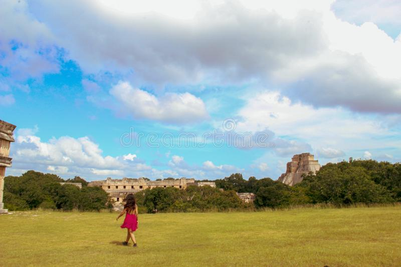 Flickan som in går, fördärvar av den forntida staden i Uxmal, Yucatan, Mexico arkivbild