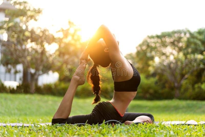 Flickan som gör yoga på solnedgången i Thailand i, parkerar royaltyfri foto